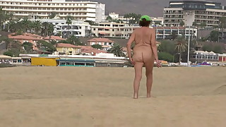 Mature woman walking on the beach naked