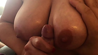 Oily dick gets jerked and cums on natural tits!